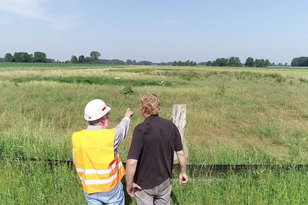 Zwei Menschen stehen vor einem weitläufigen Feld und besprechen sich.